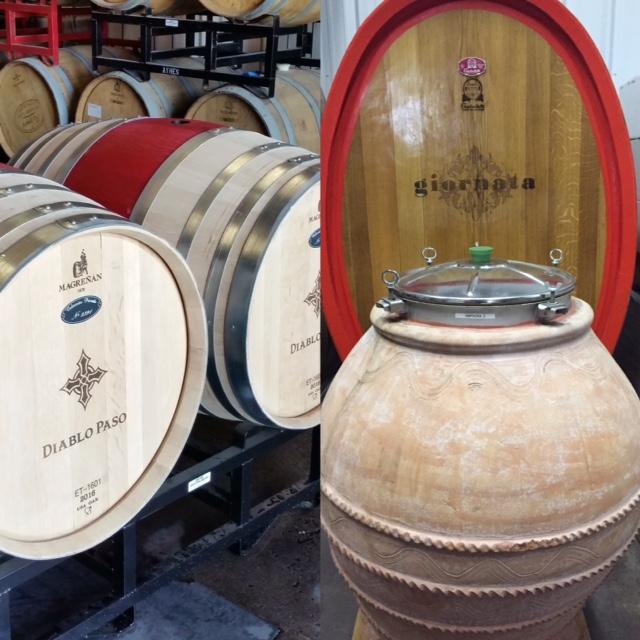 Barrels sit in a cellar; Italian amphora